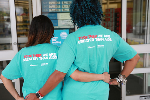 "The back of two people where blue t-shirts saying, ""Together we are greater than AIDS""."
