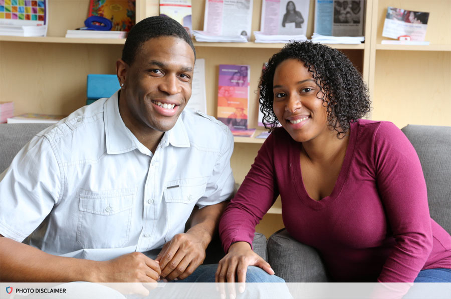 African American male and female smiling at the camera.