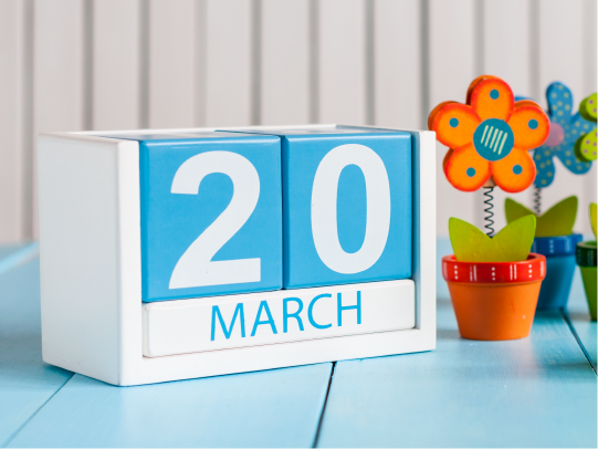 Calendar showing March 20 next to two plastic flowers