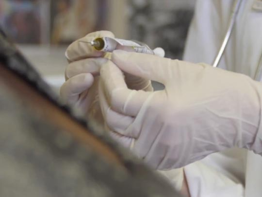A researcher prepares to administer an investigational vaccine to a clinical trial participant.