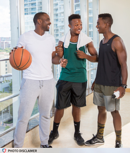 Three black men talk with each other after a basketball game