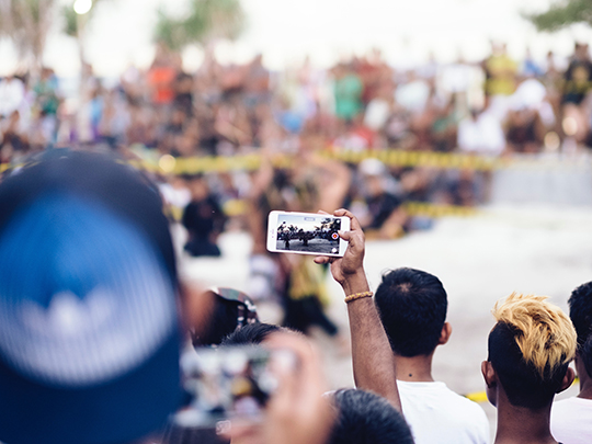 Image featuring a man holding his phone up to record something in a crowd.