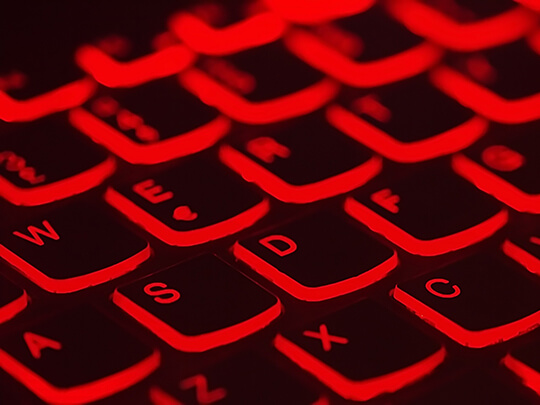 Image of keyboard lit with red light.