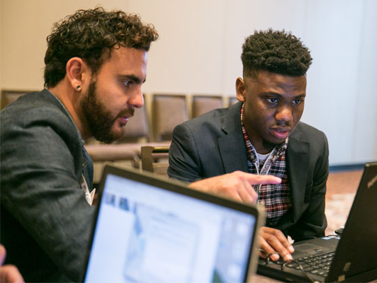 Two men look at computers at a virtual office hours session.