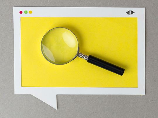 Photo of a magnifying glass on a yellow piece of paper