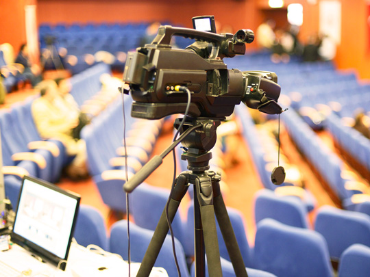 Photo of a video camera in an auditorium.