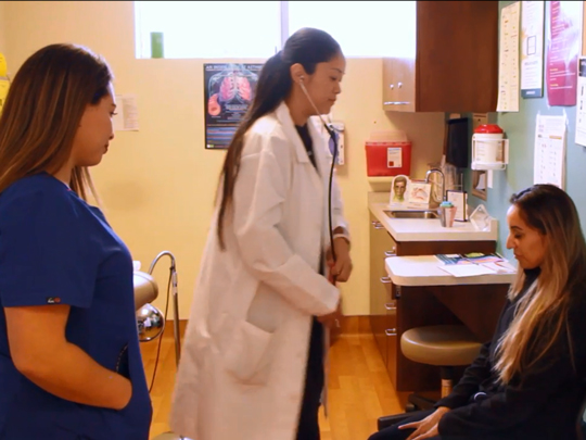 Screen grab from video showing two medical personnel working with a female patient.