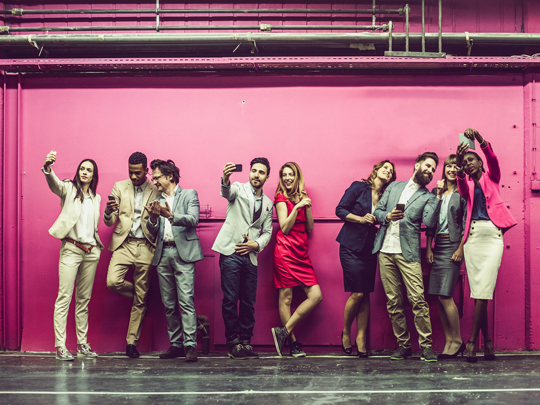 A group of people take selfies against a purple background.
