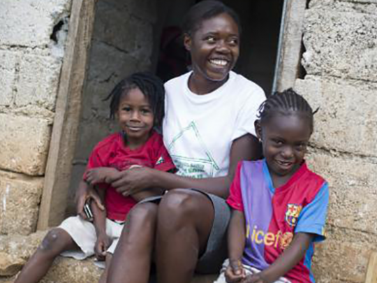 Ketcia, a community health worker, sits with children during a PEPFAR-sponsored home health care visit in Robin, Haiti.