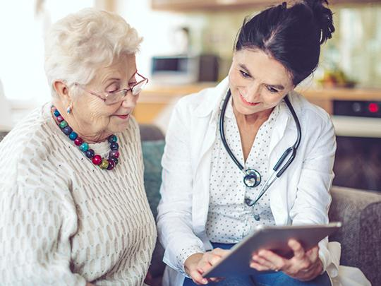 An older woman sits next to a nurse and they are both looking at a tablet.