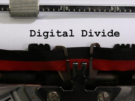 "Typewriter with the text ""Digital Divide"" typed on the paper."