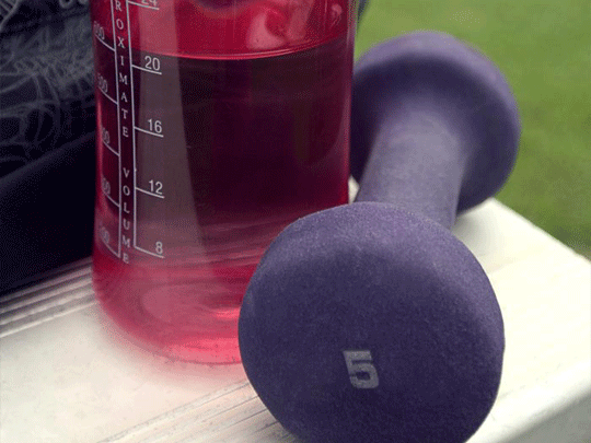 Taken at an outdoor Georgia running track, this image depicts a partially-filled red plastic water bottle, along-side a 5lb, purple colored dumbbell.