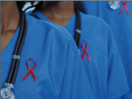 Medical personnel in blue scrubs with red AIDS ribbons.