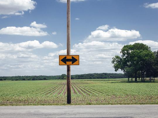 Photo of a sign with two arrows pointing in opposite directions in a rural area.