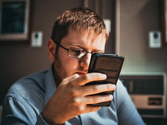 Photo of a man holding a phone up to his face.