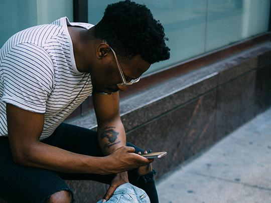 Photo of a man sitting outside looking at is phone.