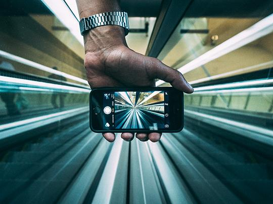 Photo of a hand holding a phone, screen facing the camera, the phone is on its camera app, showing the continuing lines of the corridor ahead and creating a continuous image from outside the phone screen to within.