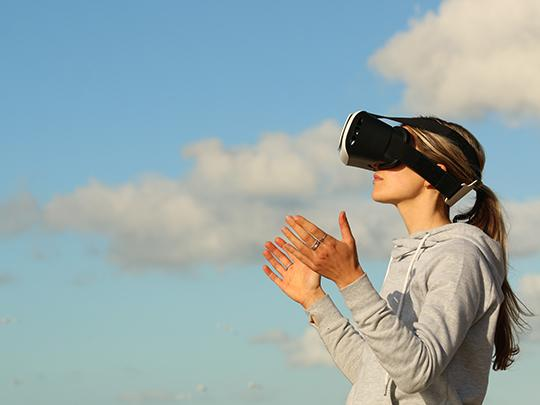 Image of a woman wearing a VR headset, extending her hands out into the blue sky.