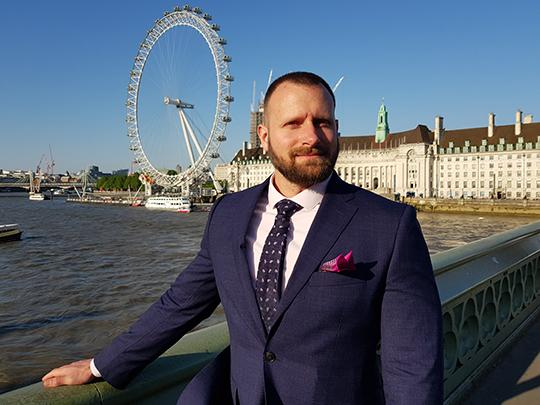 Photo of David Vaughan: a man in a suit posing in front of a bridge.