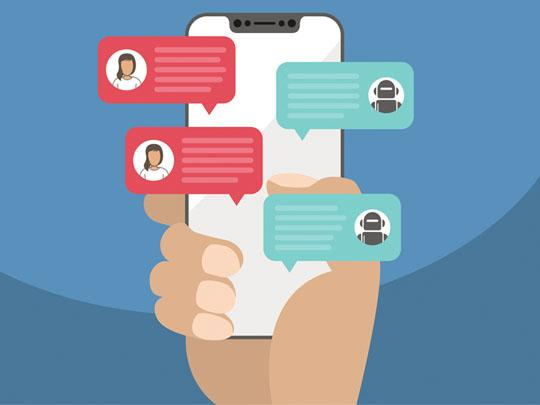 hand-holding-phone-with-chat-bot-messages-on-front