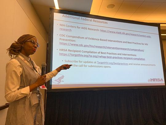 A presenter speaking in front of a projection at a HRSA session at USCA 2019.