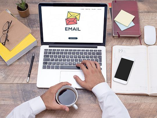 "A laptop sits on a desktop with the word, ""email"" on the screen and icons of opened and unopened emails floating across the image."
