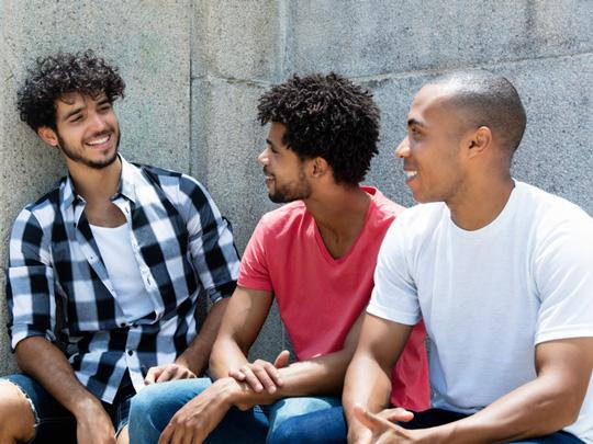 Three men sit on a bench joking together.