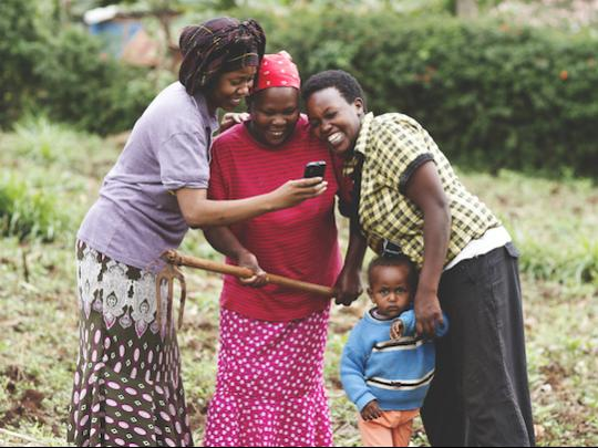 Three female farmers look at a phone.