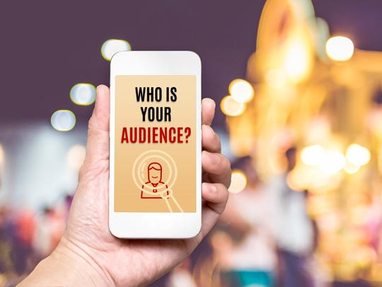 "Photo of a hand holding a smart phone with the words, ""Who is Your Audience?"""