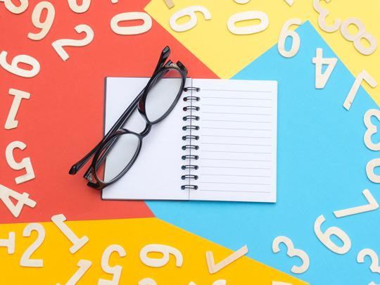Graphic of a notebook and a pair of glasses surrounded by numbers.